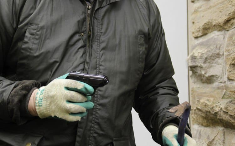 person holding gun and crowbar